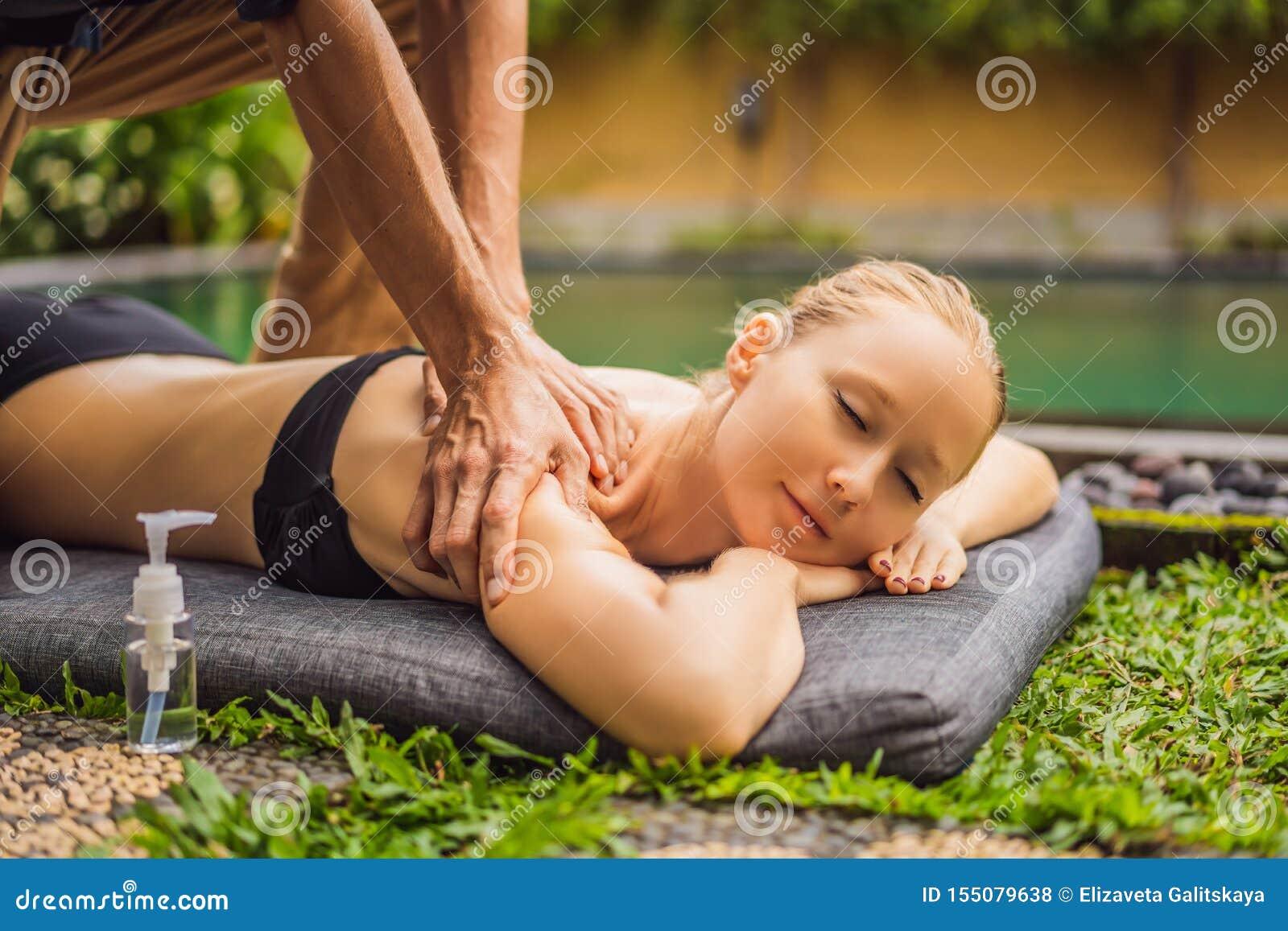 Jovem mulher que relaxa fora em uns termas da sa?de por uma piscina ao ter uma massagem