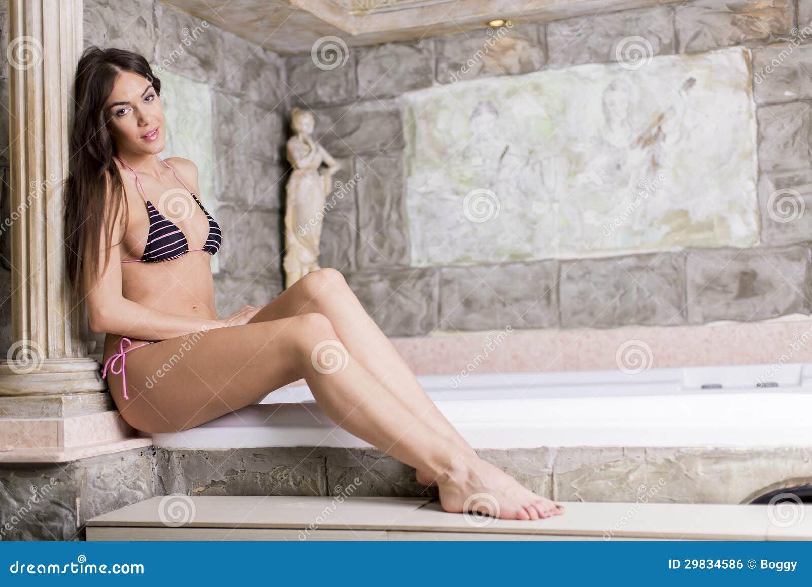 Jovem mulher bonita que relaxa na banheira de hidromassagem
