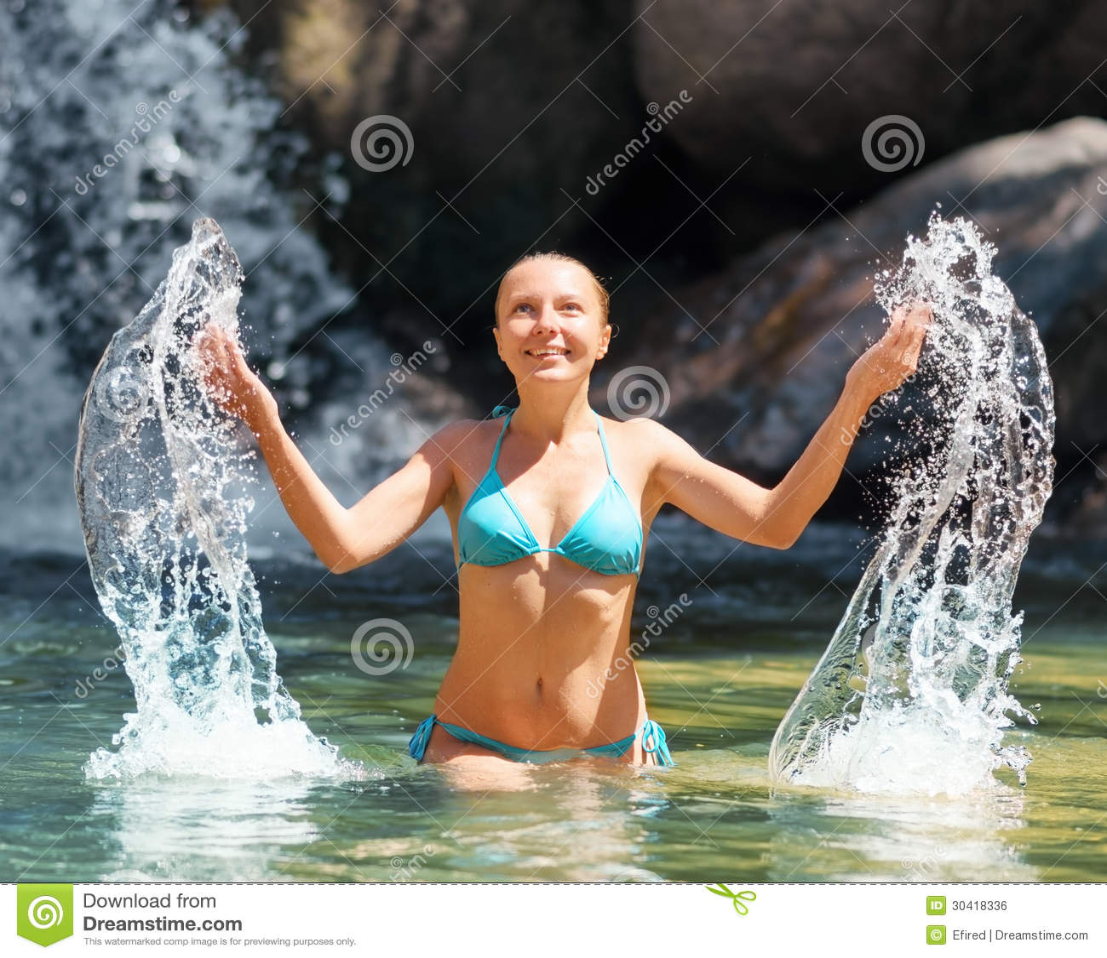 Jovem mulher que relaxa na cachoeira