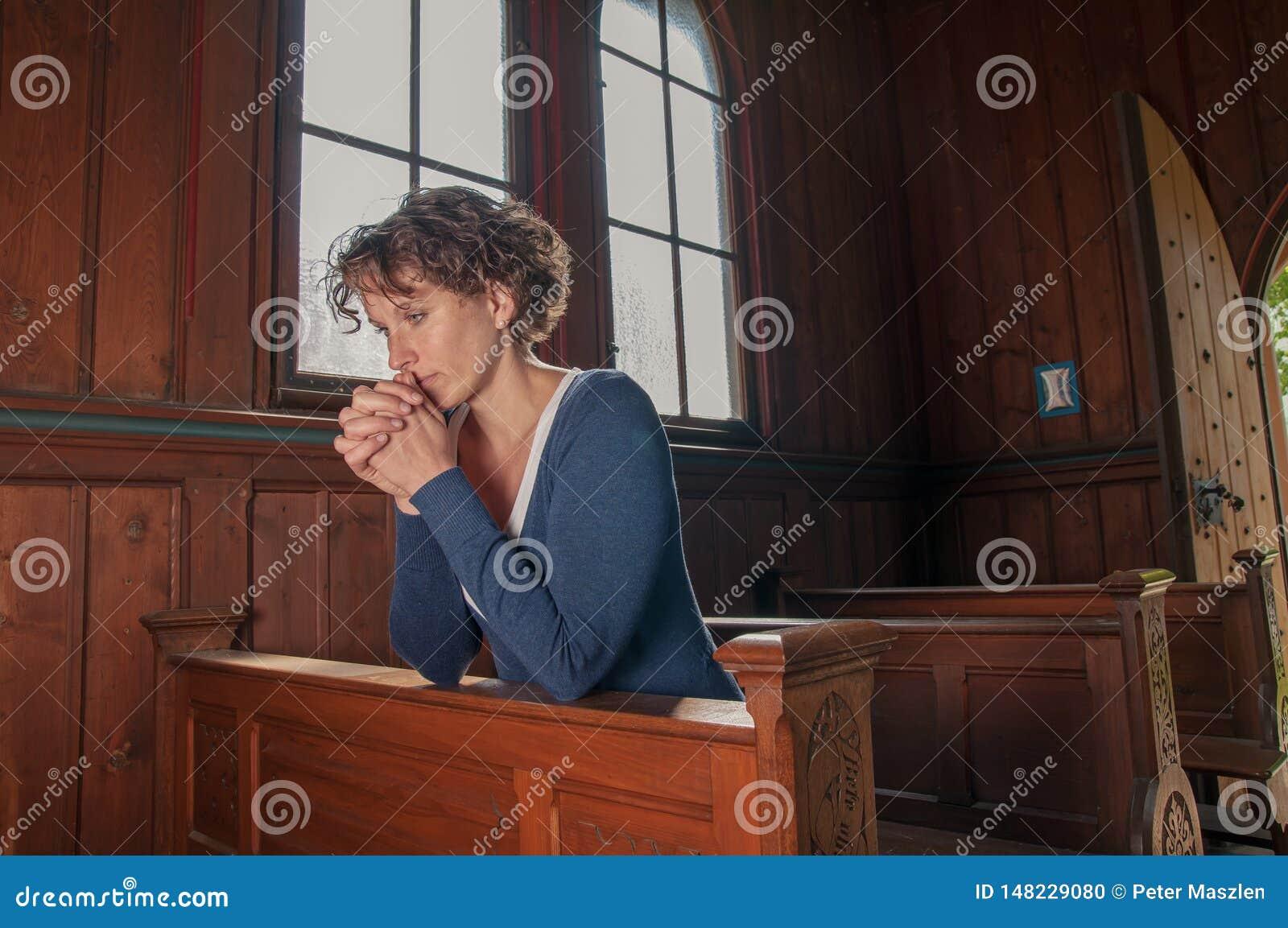 Jovem mulher que reza na igreja