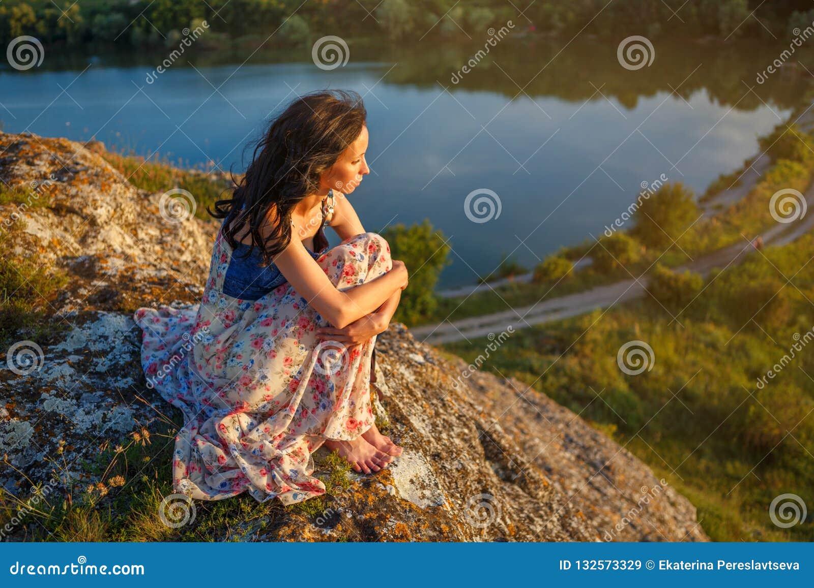 Jovem mulher que senta-se em um penhasco que negligencia o lago, humor triste, na noite no por do sol
