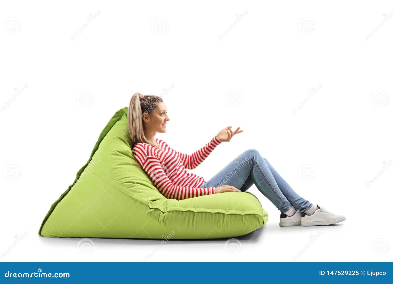 Jovem mulher que senta-se em um saco de feijão e que gesticula com mão