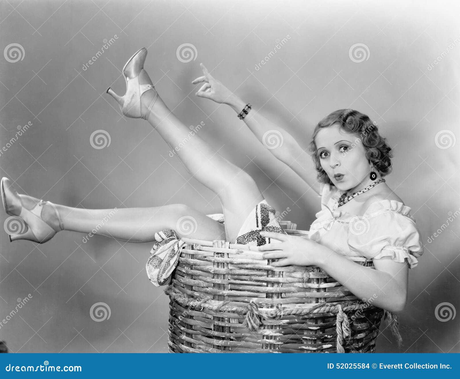 Jovem mulher que senta-se em uma cesta que olha surpreendida (todas as pessoas descritas não são umas vivas mais longo e nenhuma