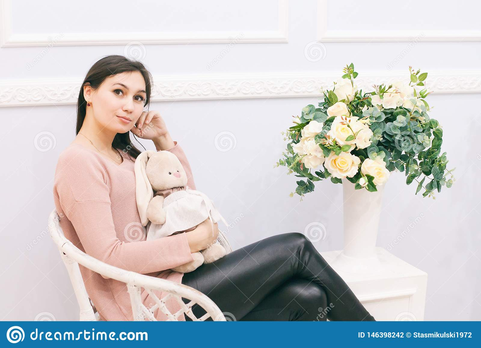 Jovem mulher que senta-se na cadeira de vime em casa