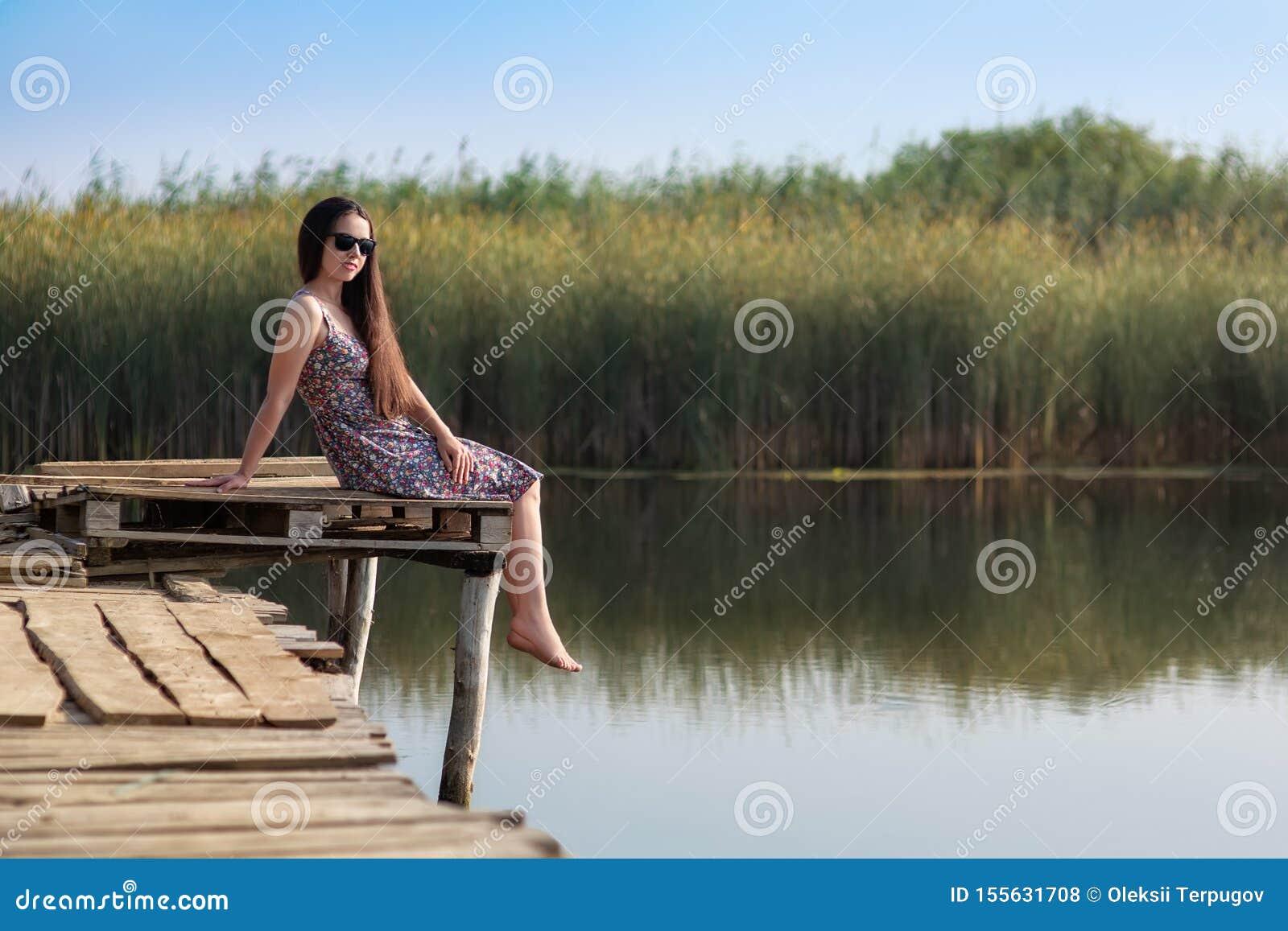 Jovem mulher que senta-se na ponte de madeira