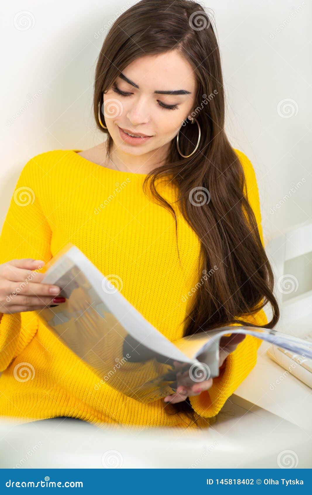 Jovem mulher que senta-se no local de trabalho e que l? o papel no escrit?rio