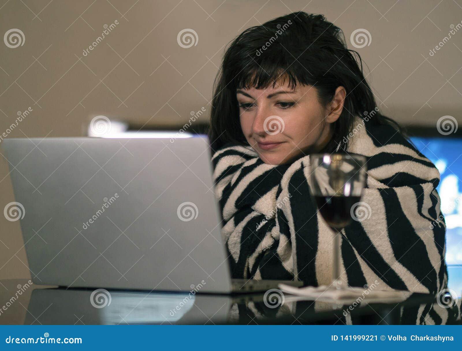 Jovem mulher que sorri ao sentar-se em casa pela tela do portátil