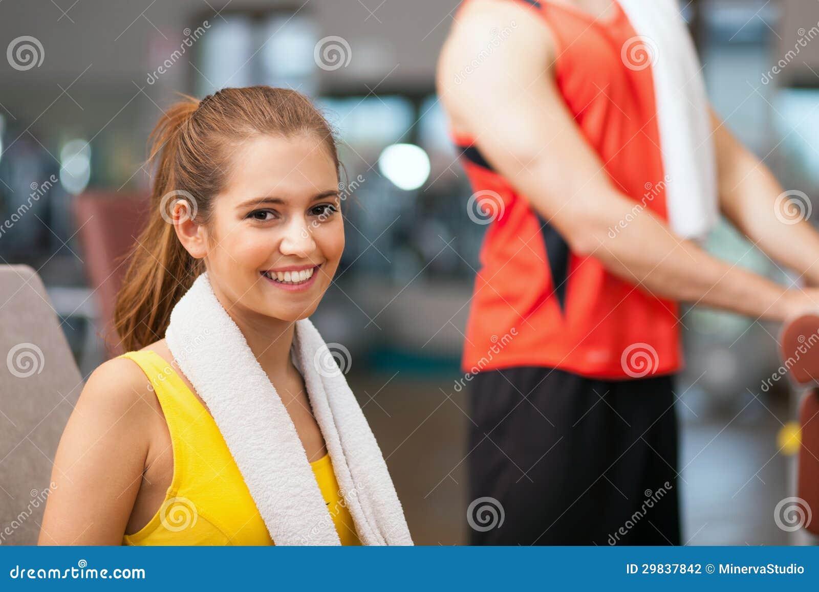 Mulher que sorri em um clube de aptidão