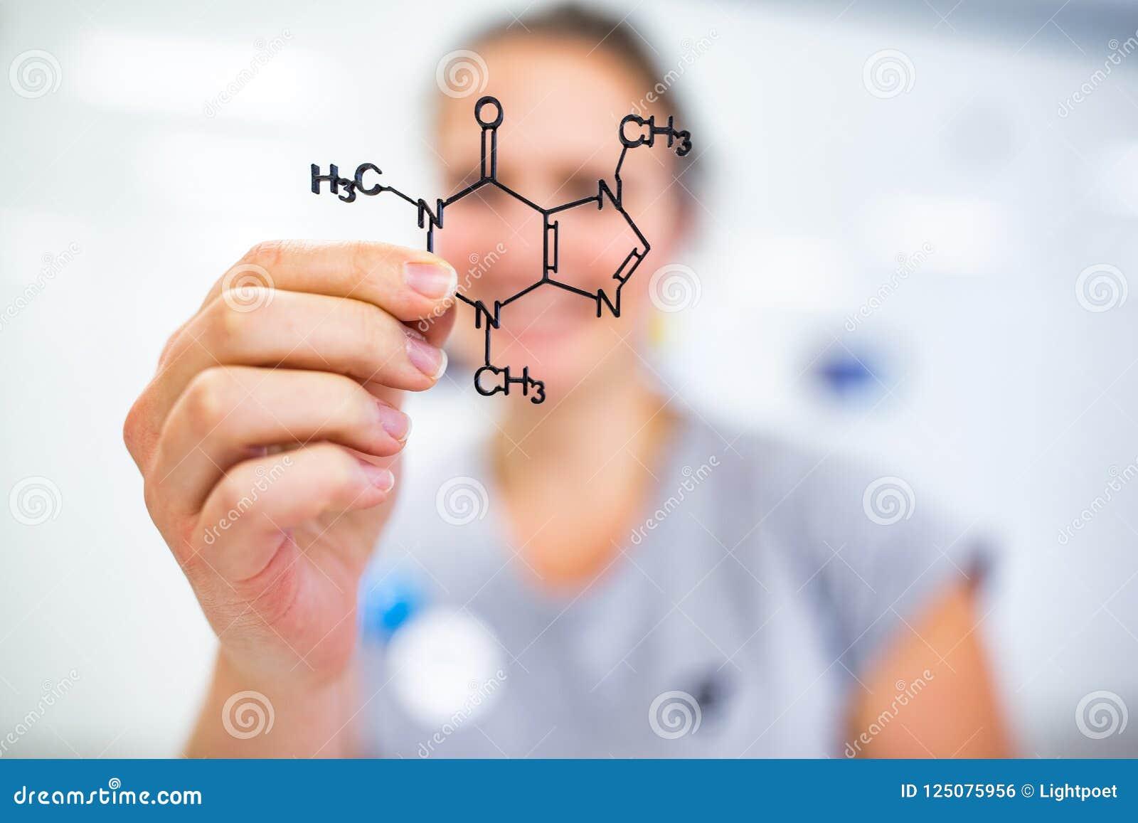 Jovem mulher que sustenta um modelo molecular