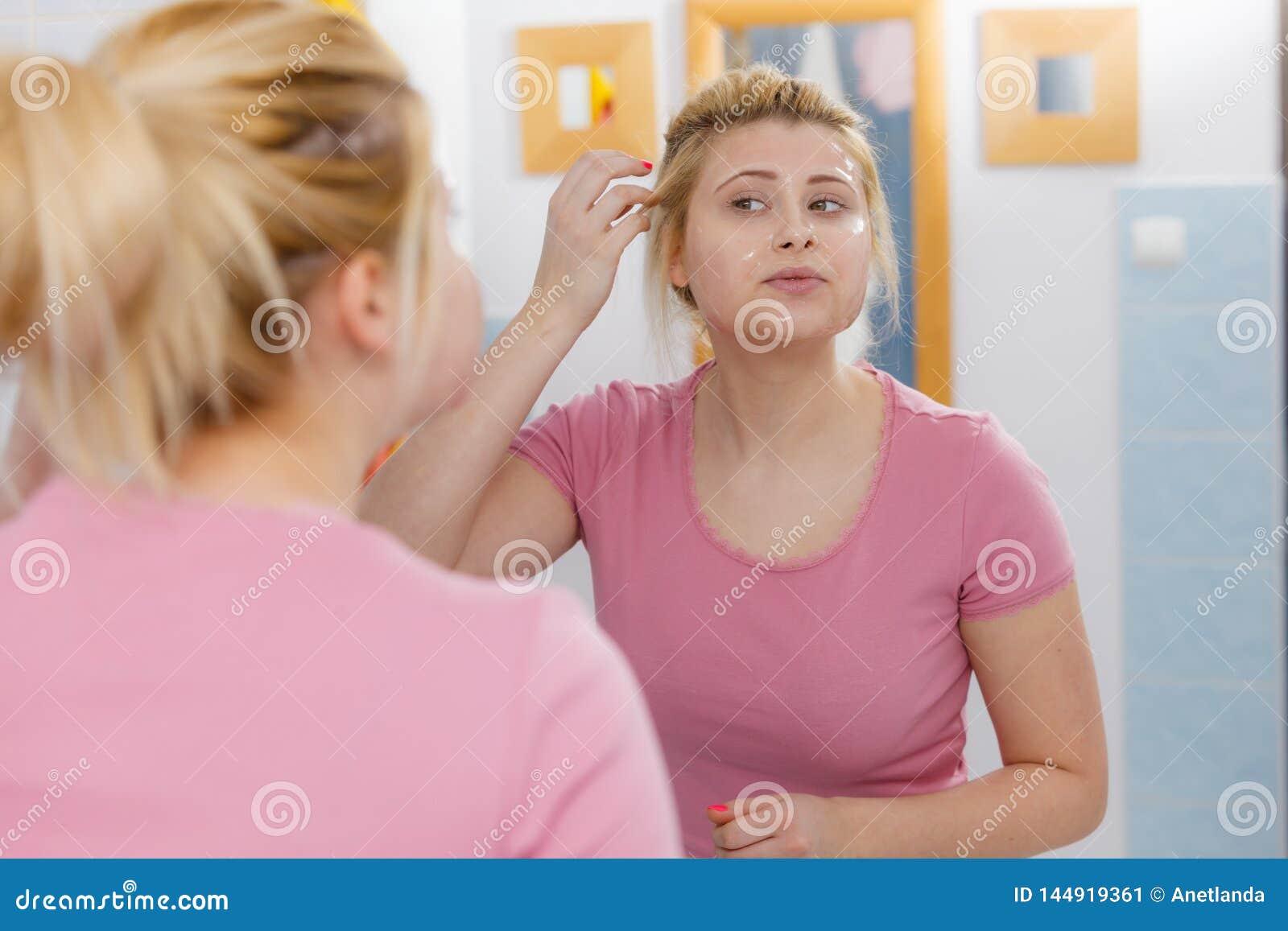 Jovem mulher que tem a m?scara do gel na cara