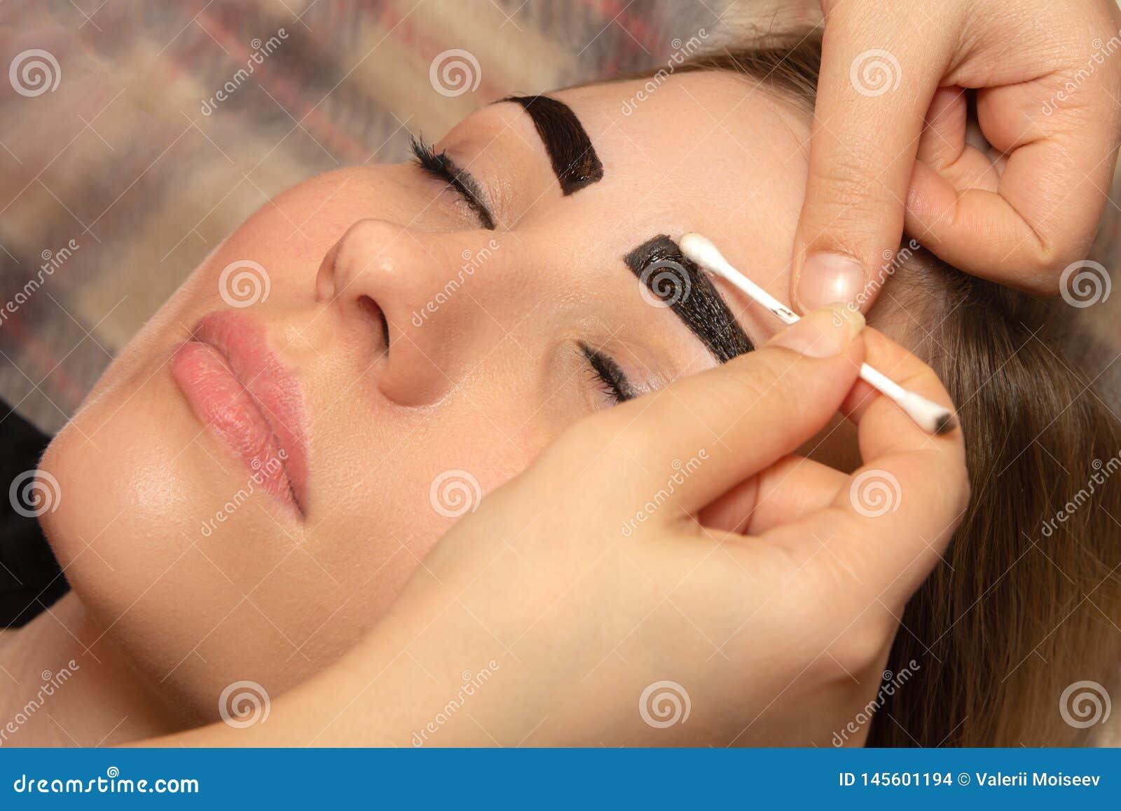 Jovem mulher que tem o procedimento profissional da corre??o da sobrancelha no sal?o de beleza