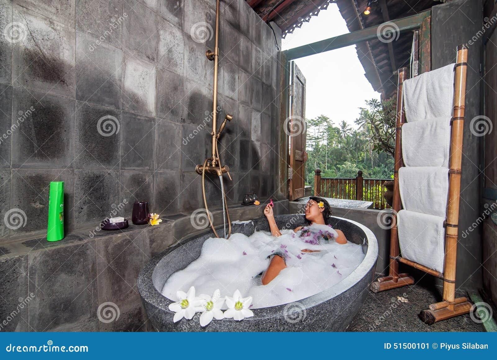 Jovem mulher que tem um banho