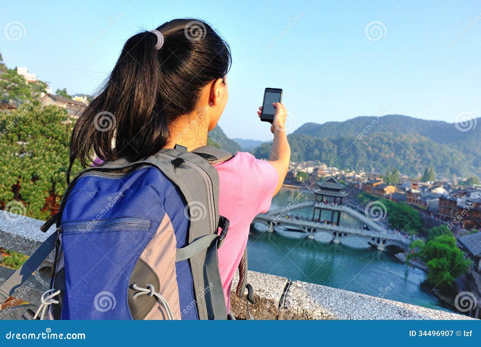 Jovem mulher que toma a foto com o telefone esperto no fenghuang t antigo