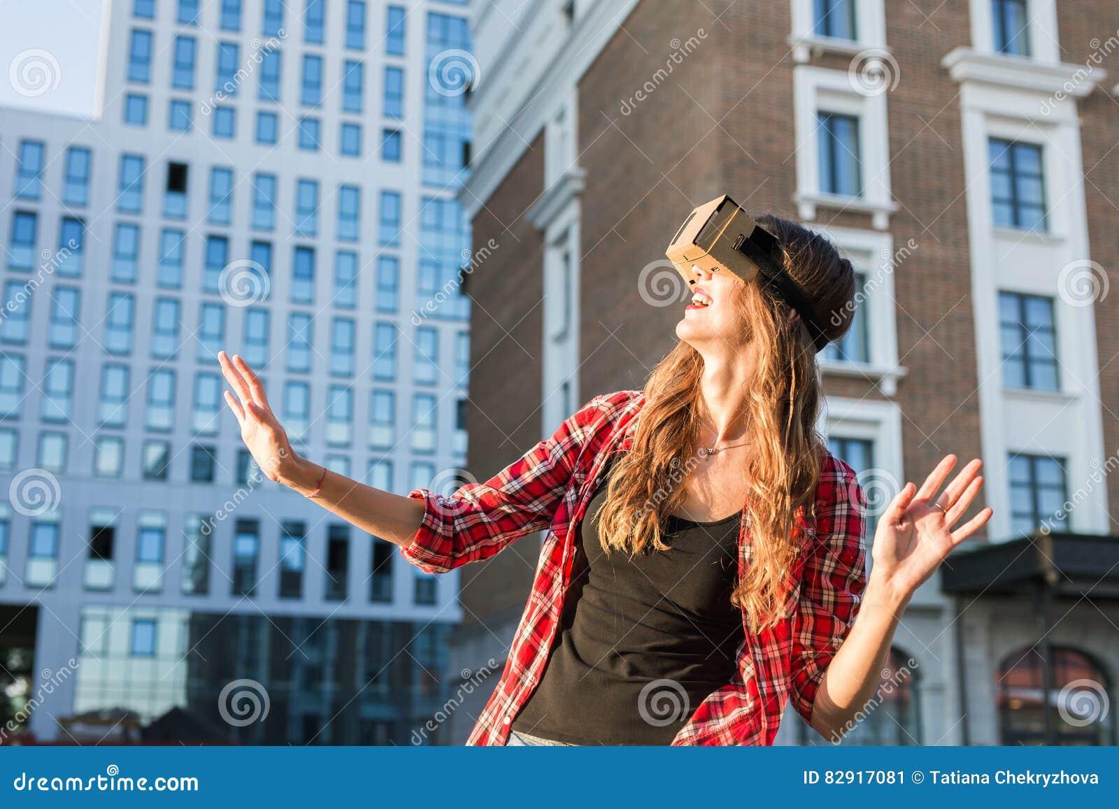 Jovem mulher que usa a elevação - vidros da realidade virtual da tecnologia exteriores