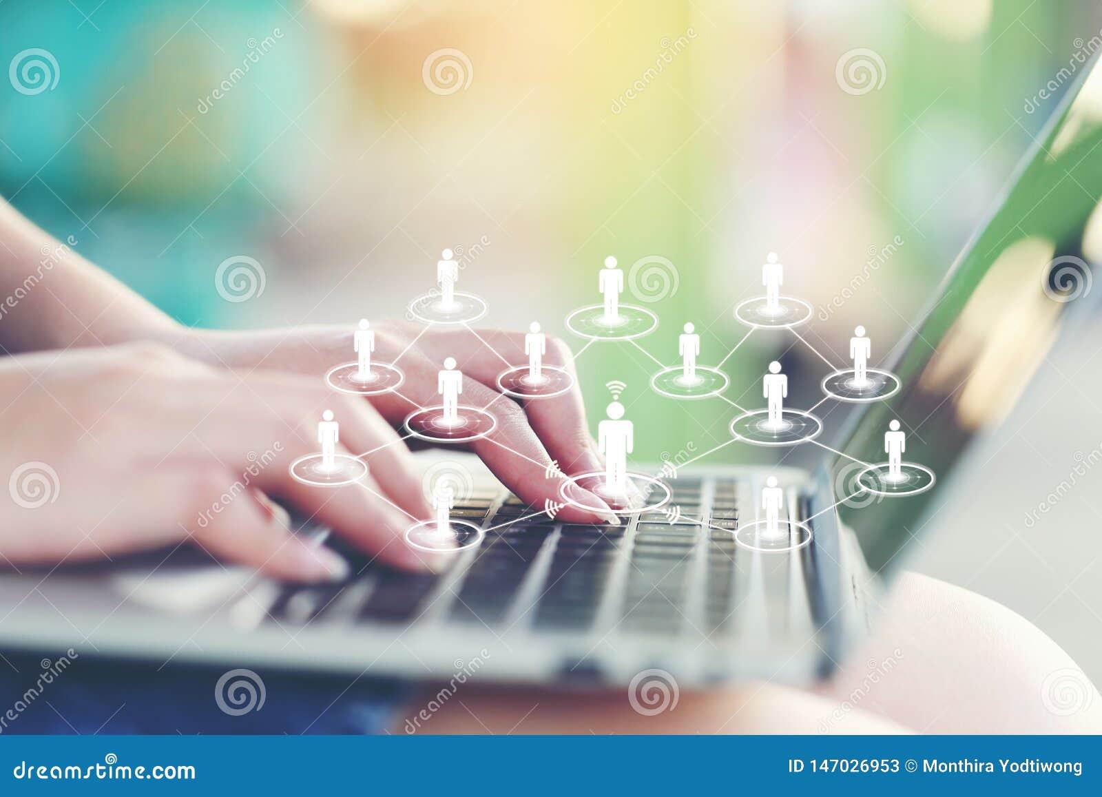 Jovem mulher que usa o laptop e o ícone ou o holograma na cafetaria, no Internet social e no negócio da rede de comunicação dos m