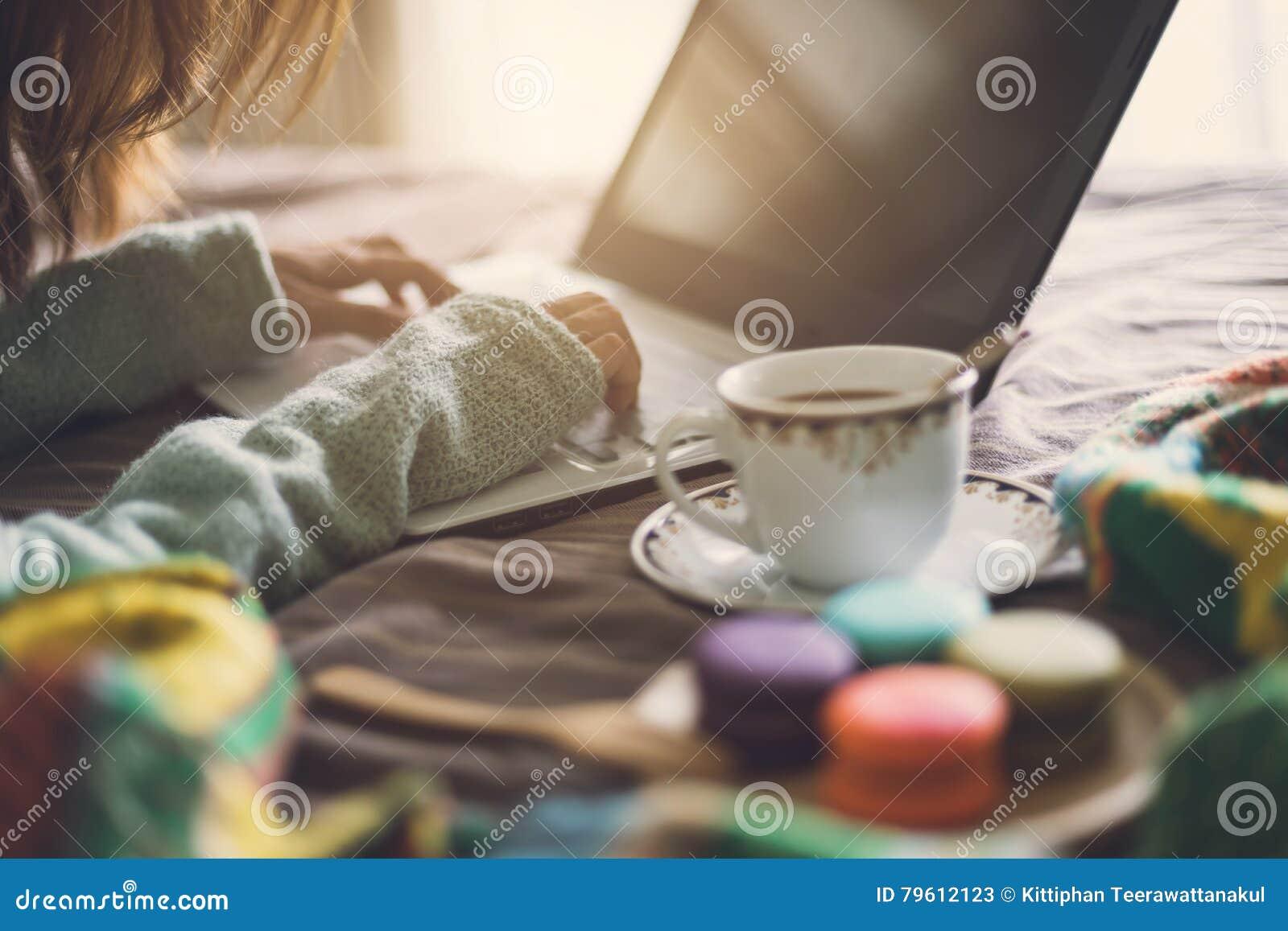 Jovem mulher que usa o portátil na atmosfera home acolhedor