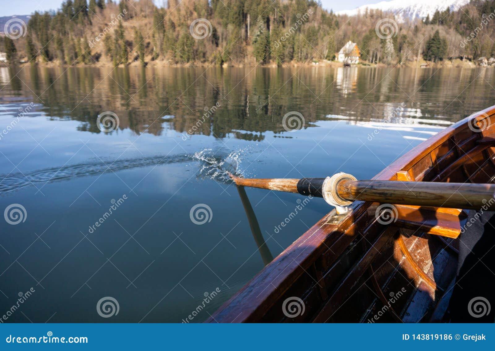 Jovem mulher que usa a p? em um barco de madeira - enfileiramento sangrado lago do Eslov?nia em barcos de madeira