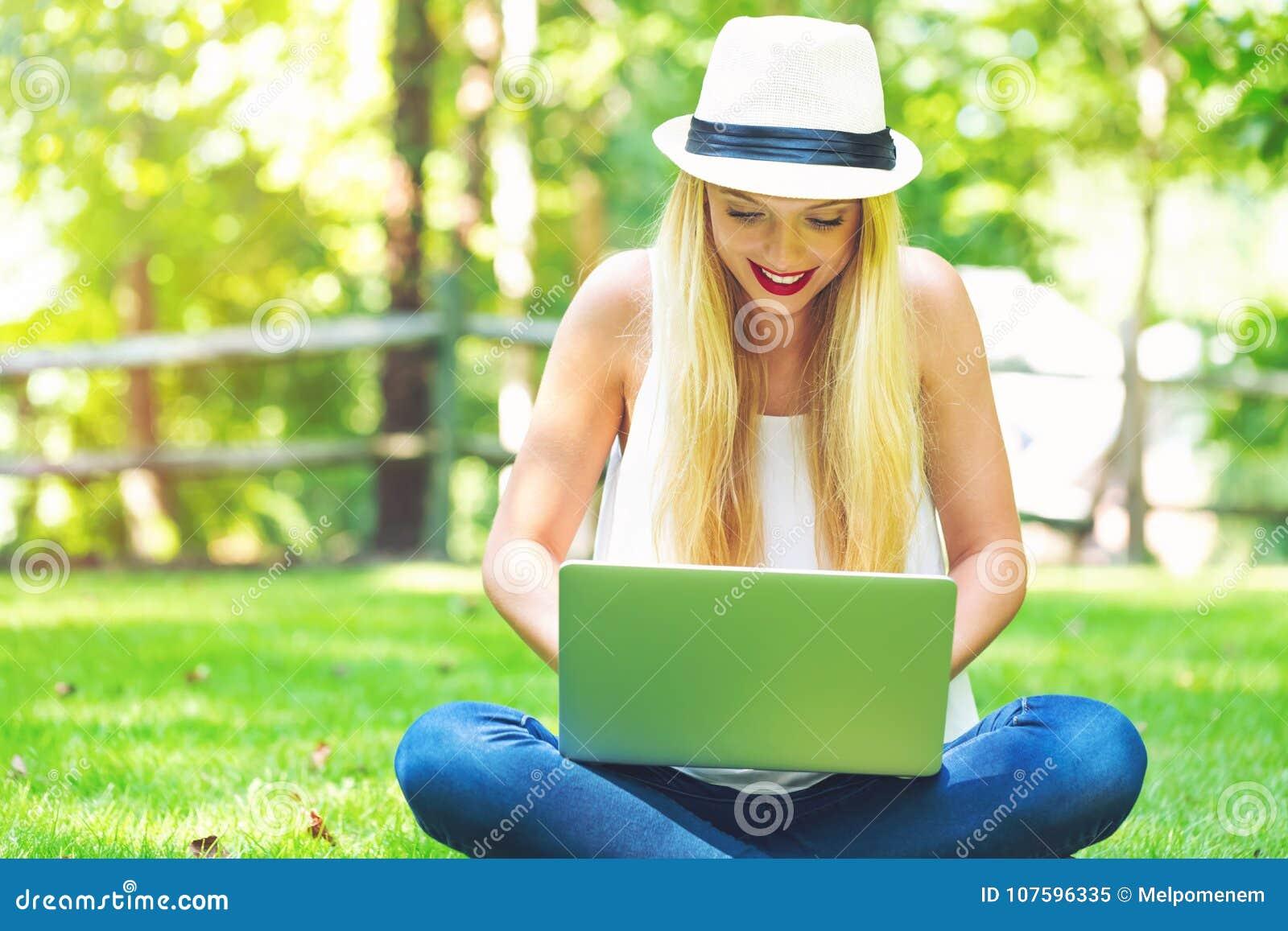Jovem mulher que usa seu portátil fora