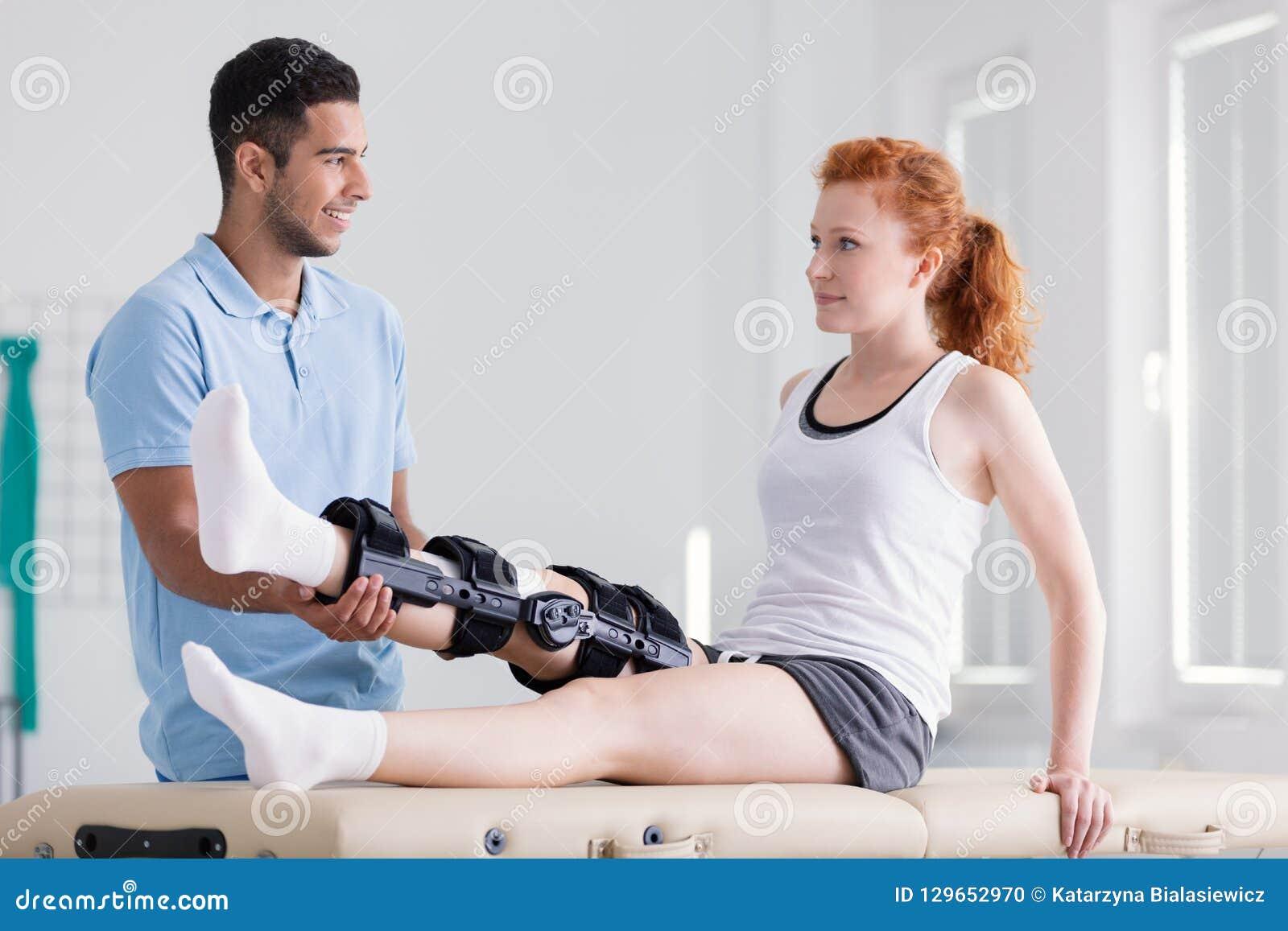 Jovem mulher que veste uma cinta durante a reabilitação com seu fisioterapeuta