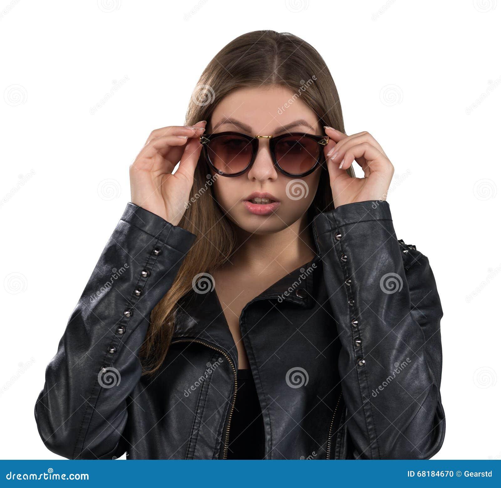 Jovem mulher quente glamoroso em um casaco de cabedal e em uns óculos de sol marrons, isolados no fundo branco Rua, forma da roch