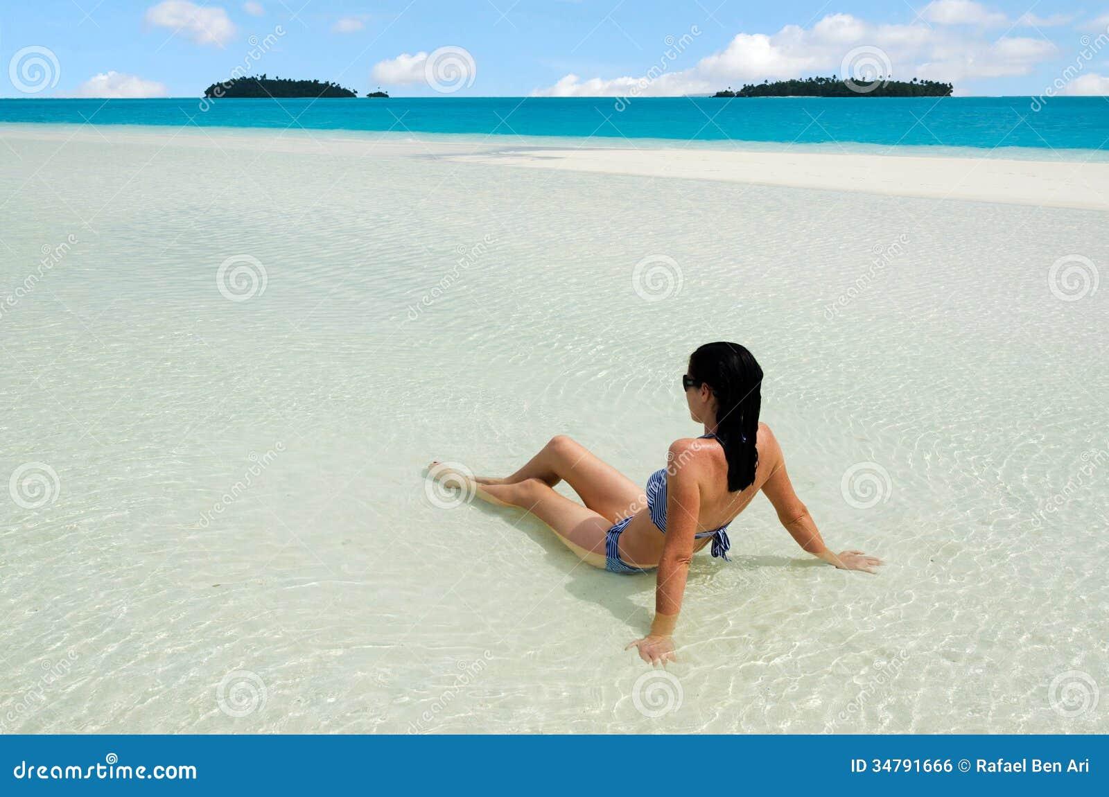 A jovem mulher relaxa no cozinheiro Islands da lagoa de Aitutaki