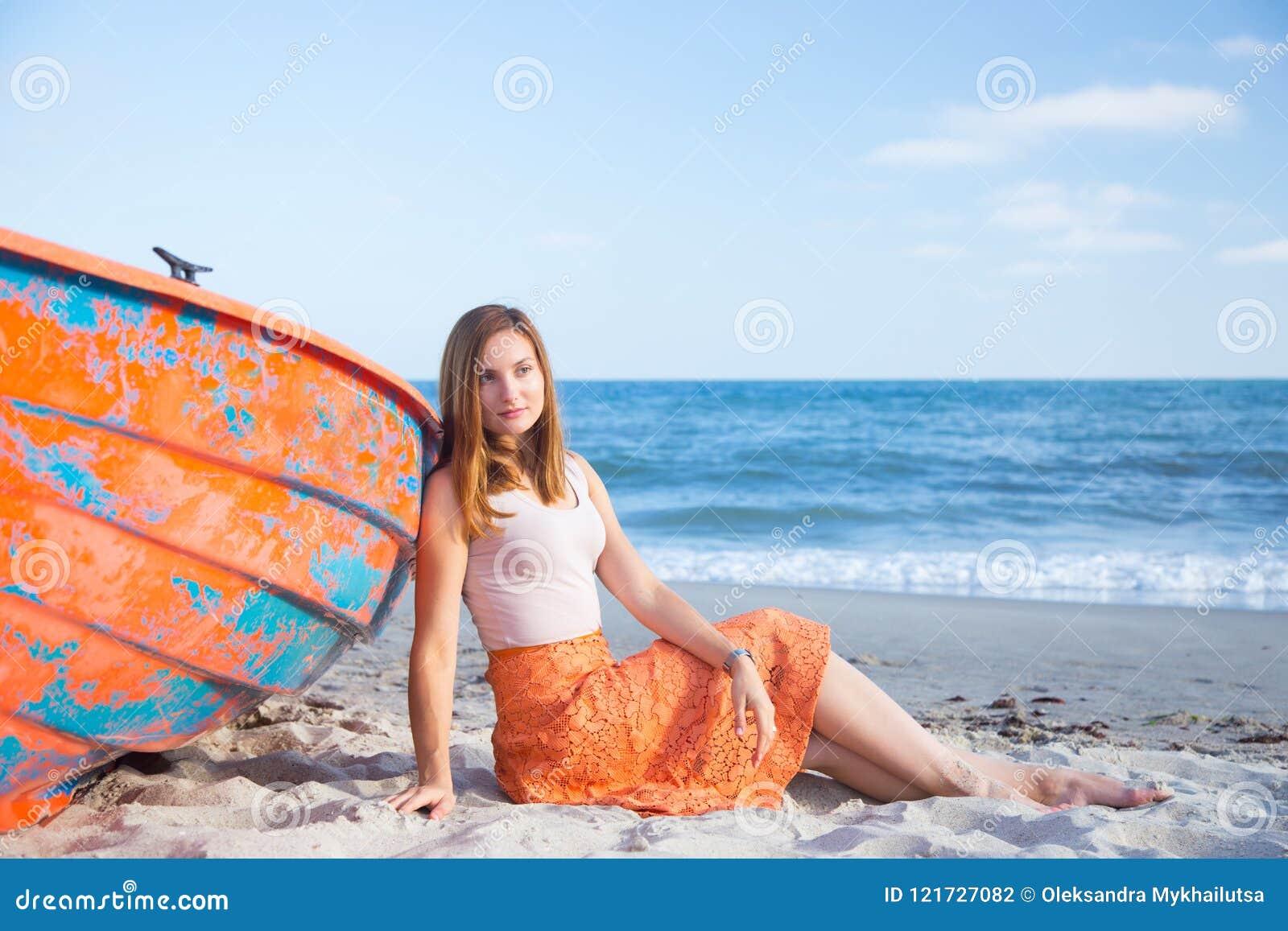 Jovem mulher ruivo bonita na saia que relaxa na praia perto do barco alaranjado