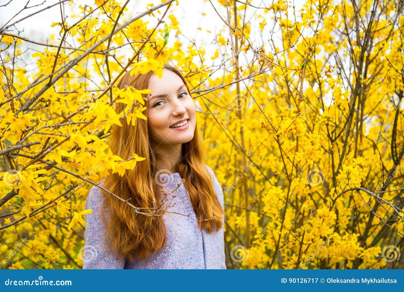Jovem mulher ruivo bonita que está perto de Forsythi de florescência