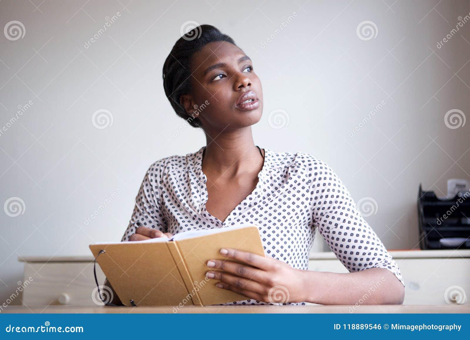 Jovem mulher séria que pensa e que escreve no jornal