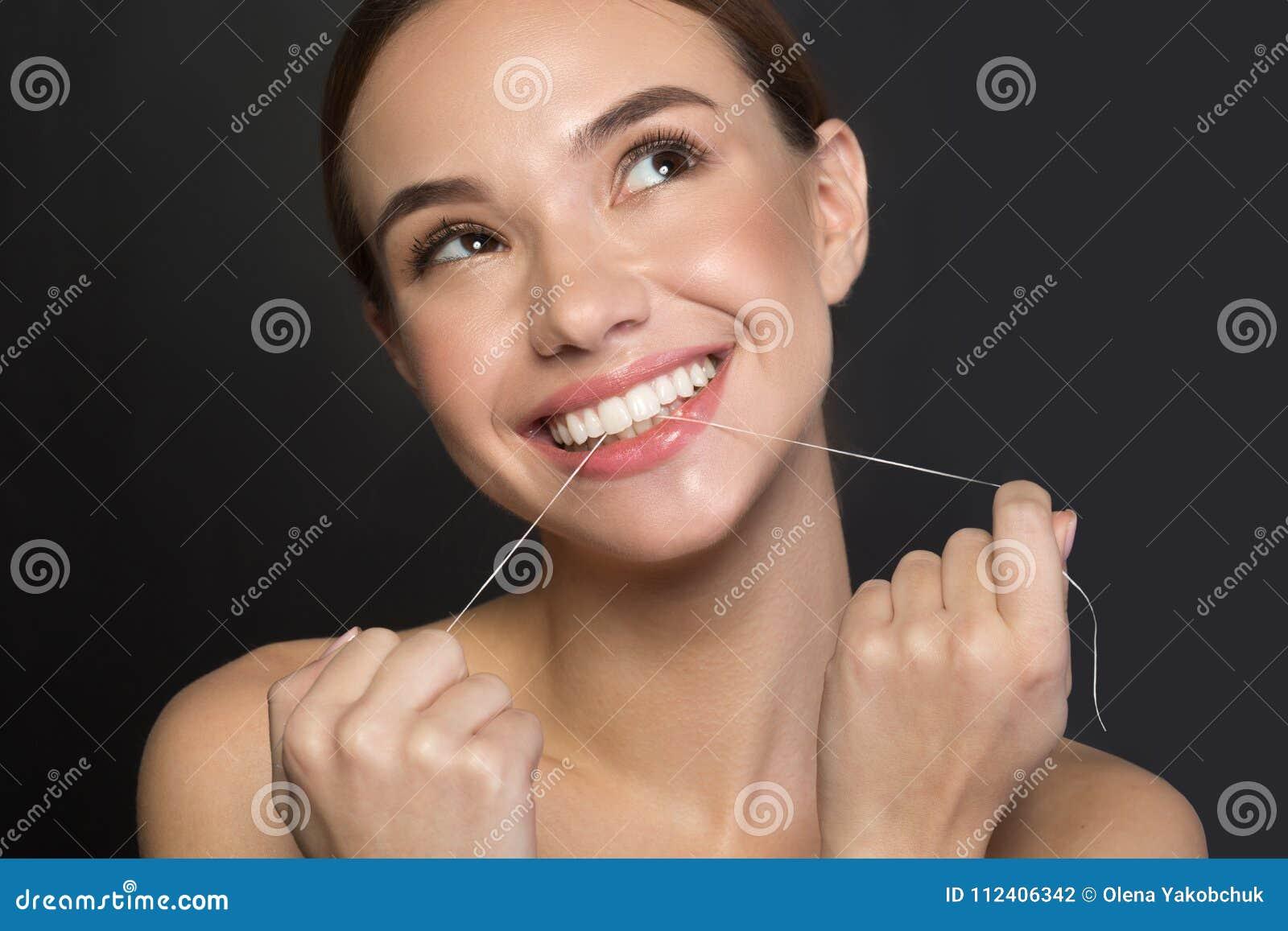 439a42b20 O retrato da menina bonito entusiasmado é estando e de utilização o fio  dental para os dentes de limpeza Está olhando de lado com alegria e sorriso  Isolado ...
