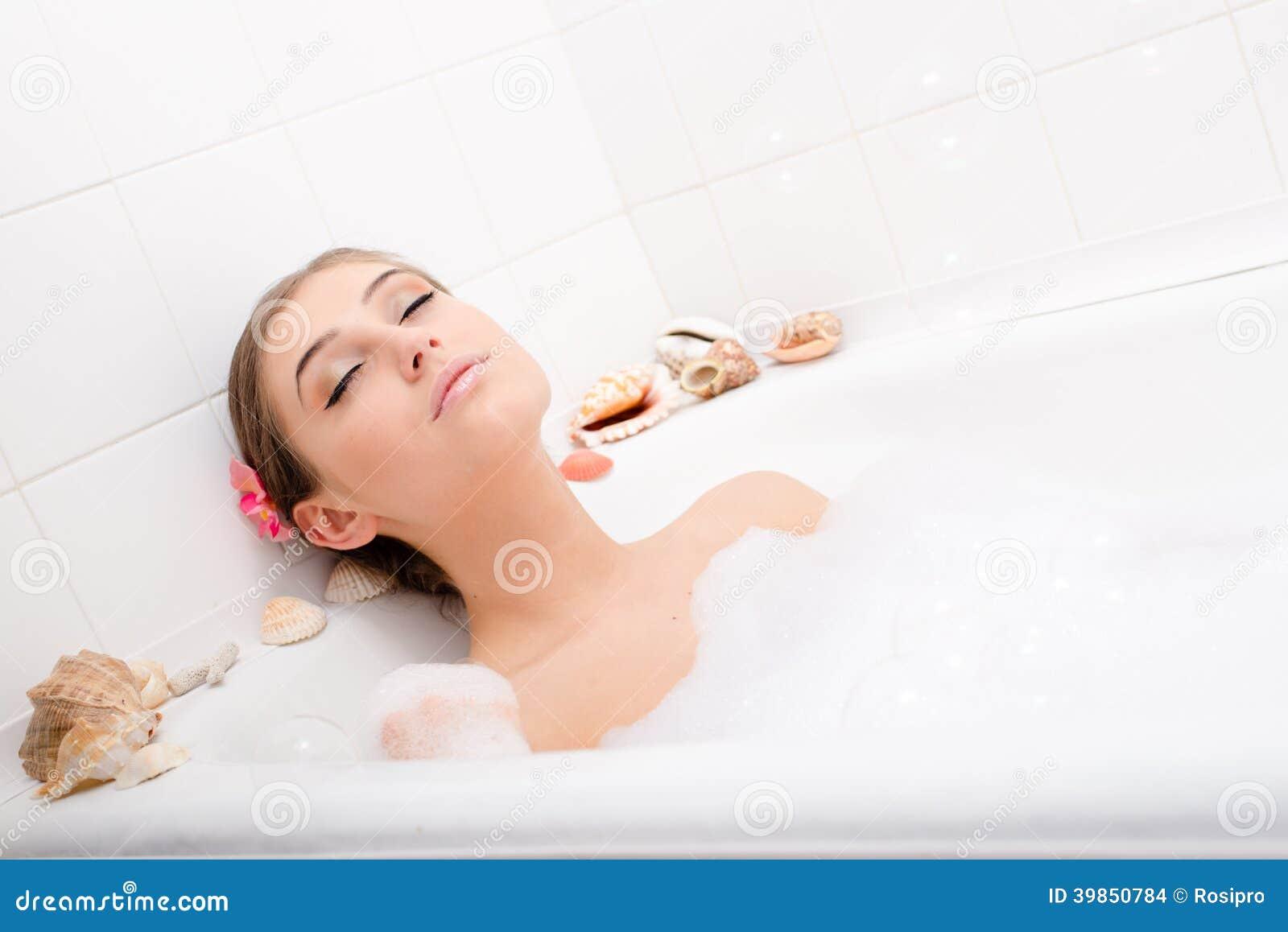 A jovem mulher  sexy  atrativa de relaxamento que encontra-se no banho com a espuma, apreciando o tratamento do abrandamento dos