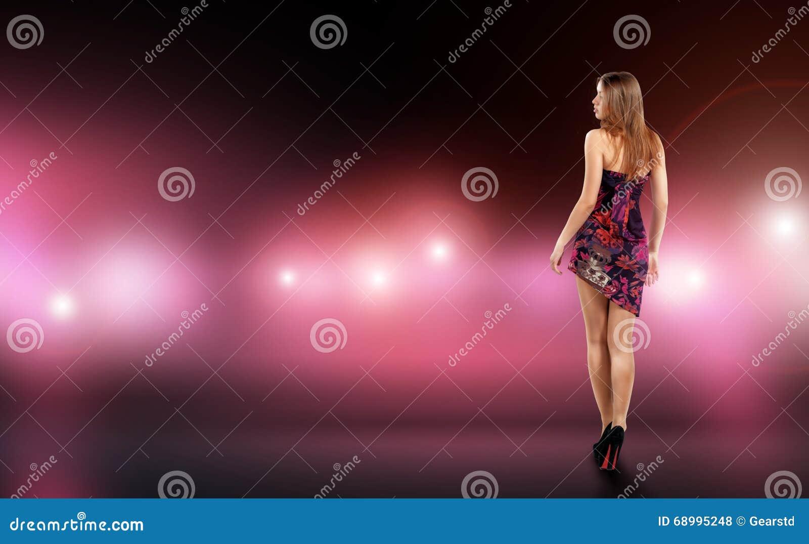A jovem mulher  sexy  no vestido do encaixe cercado pelo cuidado e a câmera piscam Celebridade, modelo, estrela
