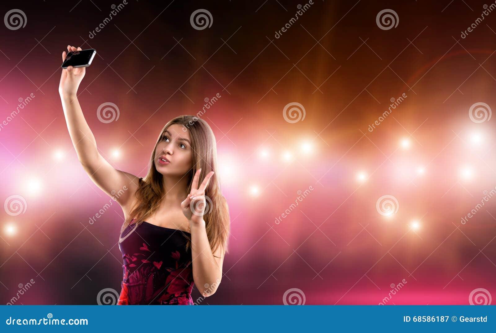 Jovem mulher  sexy  no vestido que faz o selfie, cercado pelo cuidado e pelo flash da câmera