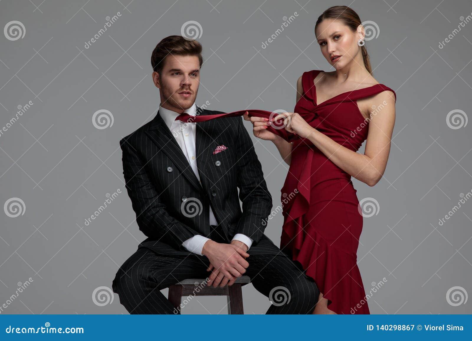 Jovem mulher  sexy  que joga com o laço do seu homem