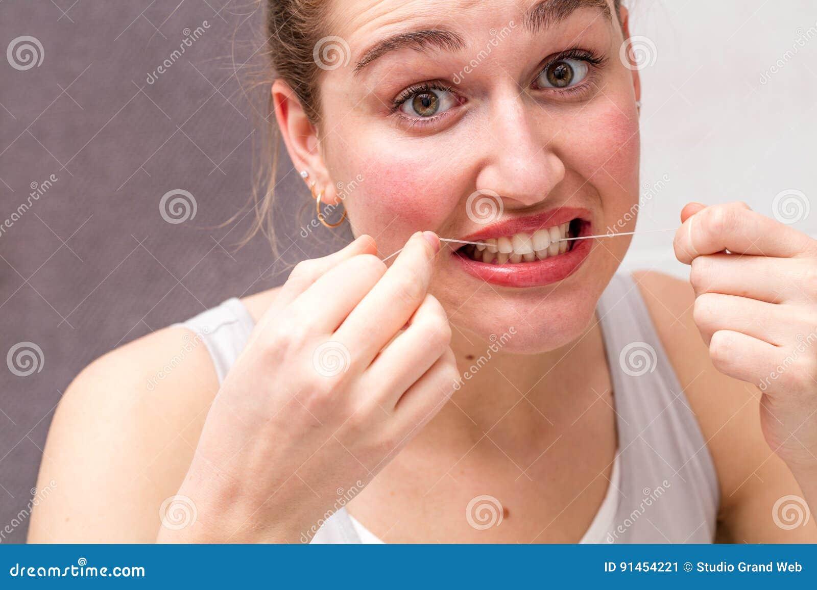 fad9cf243 Close up de uma jovem mulher bonita surpreendida que mói seus dentes em  usar o fio dental para importar-se e limpar seus dentes para a higiene
