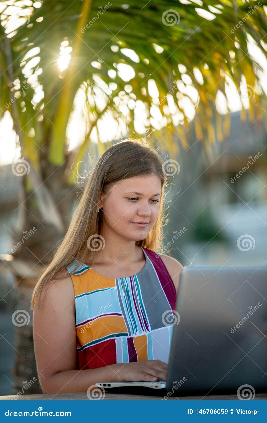 A jovem mulher trabalha no computador