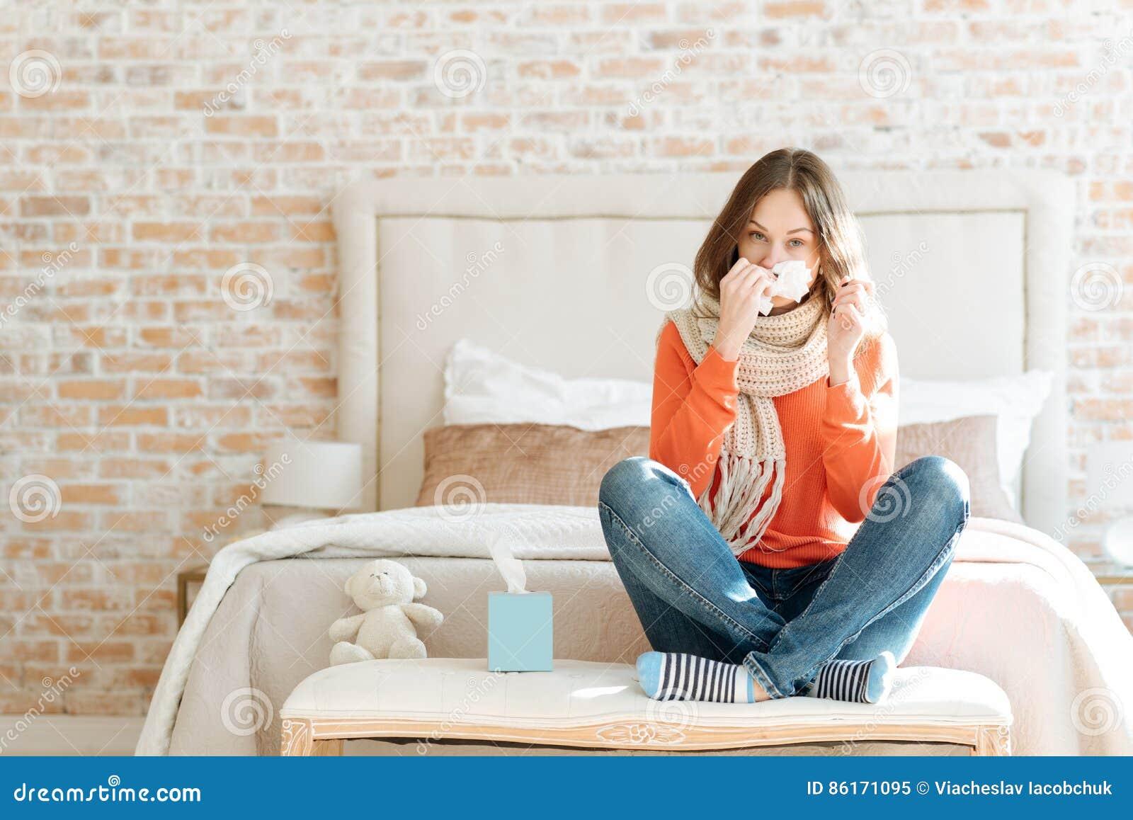 Jovem mulher virada que sofre da gripe em casa