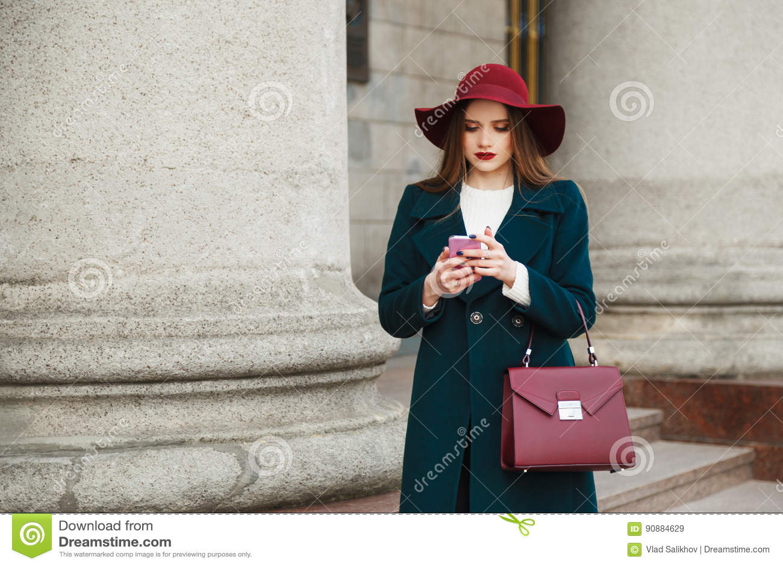 A jovem senhora bonita da forma veste o chapéu e o revestimento no smartphone clássico do uso do estilo