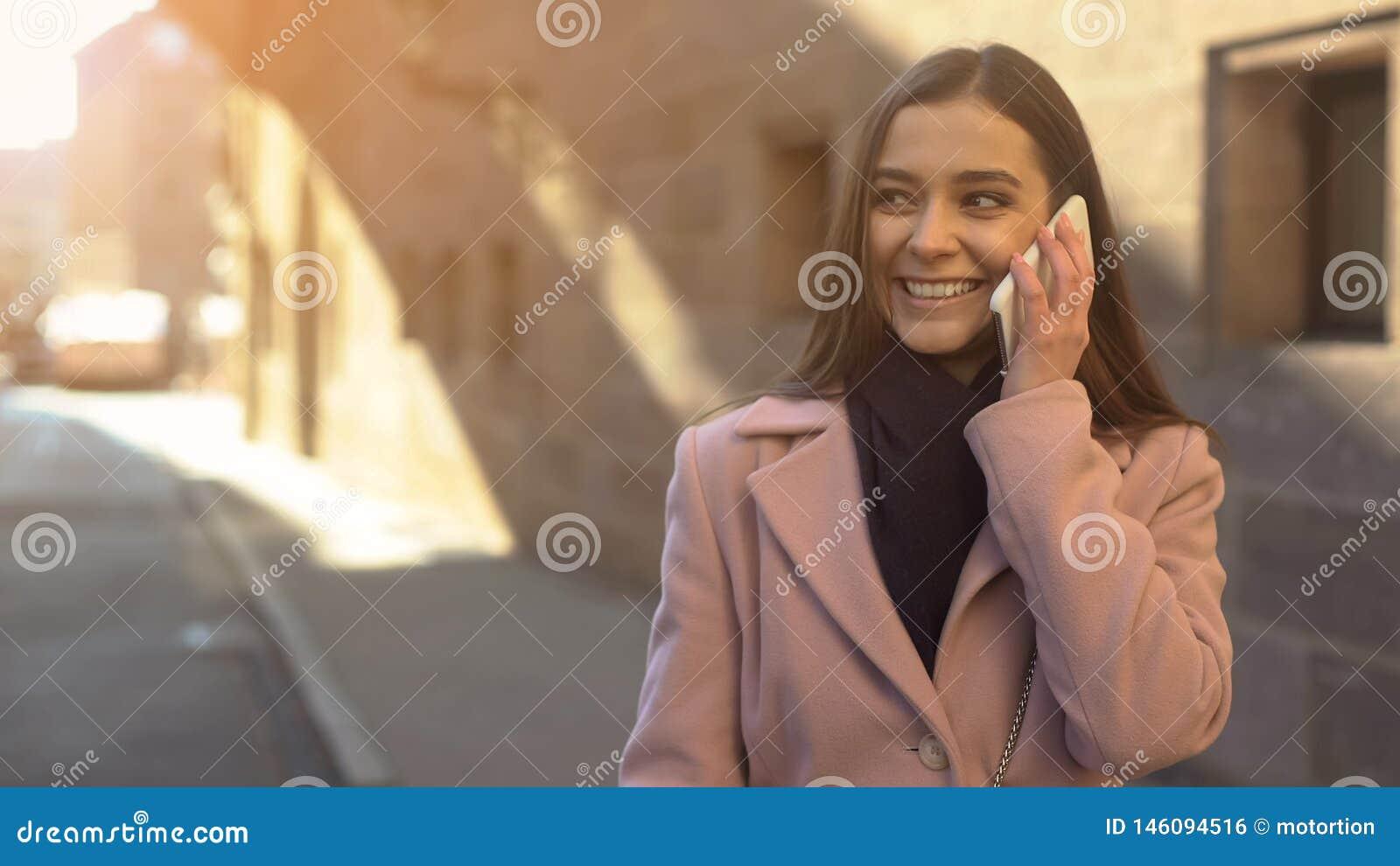 Jovem senhora bonita que fala no telefone, andando na baixa da cidade antiga, vagueando