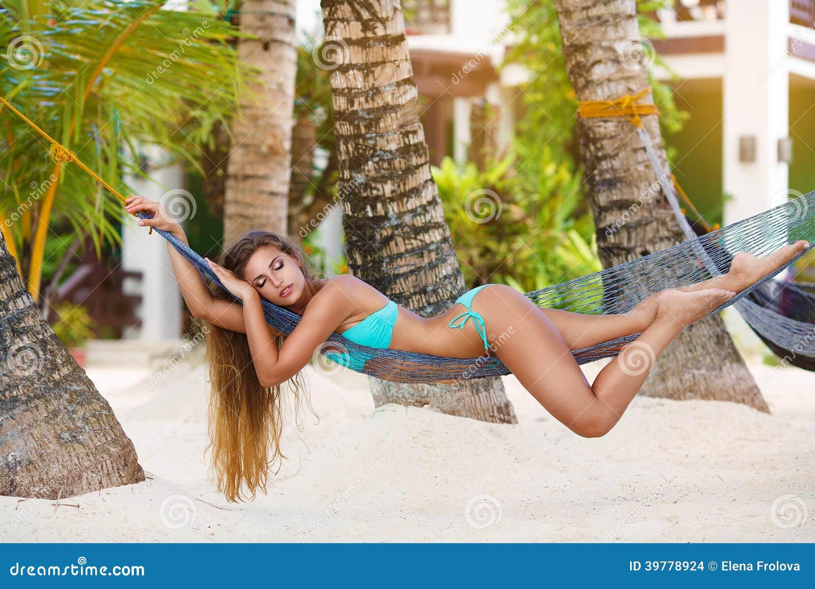 Jovem senhora com o cabelo louro longo que relaxa na rede no trop