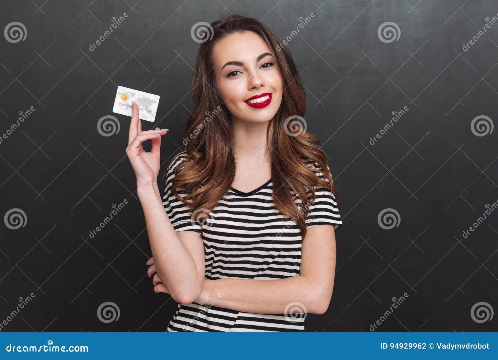 Jovem senhora de sorriso sobre a parede cinzenta que guarda o cartão de crédito