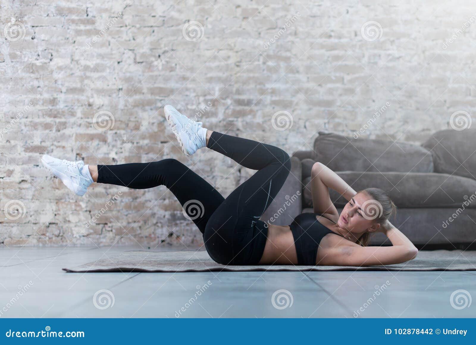 Jovem senhora desportivo que faz o exercício cruzado da trituração que encontra-se em um tapete no estúdio moderno