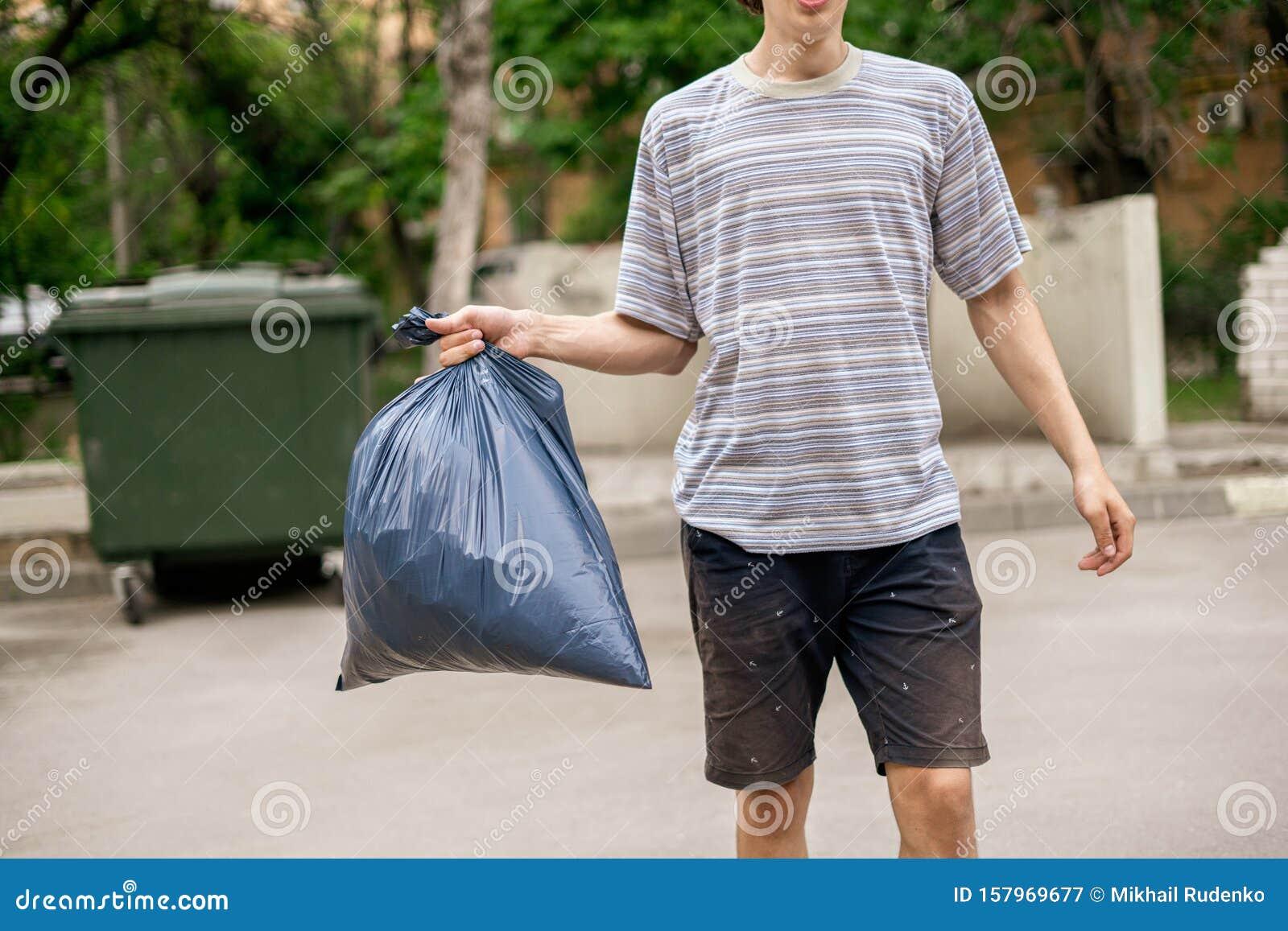 ¿Cómo estas hoy? en imagenes. - Página 8 Joven-sacando-bolsas-de-basura-con-tomando-una-bolsa-157969677
