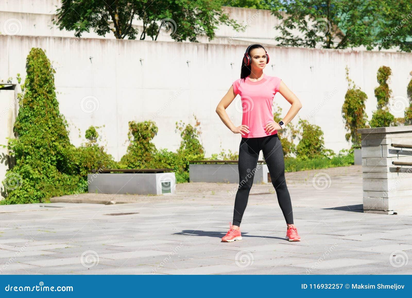 Jovens, ajuste e menina desportiva na rua Aptidão, esporte, movimentar-se urbano e conceito saudável do estilo de vida