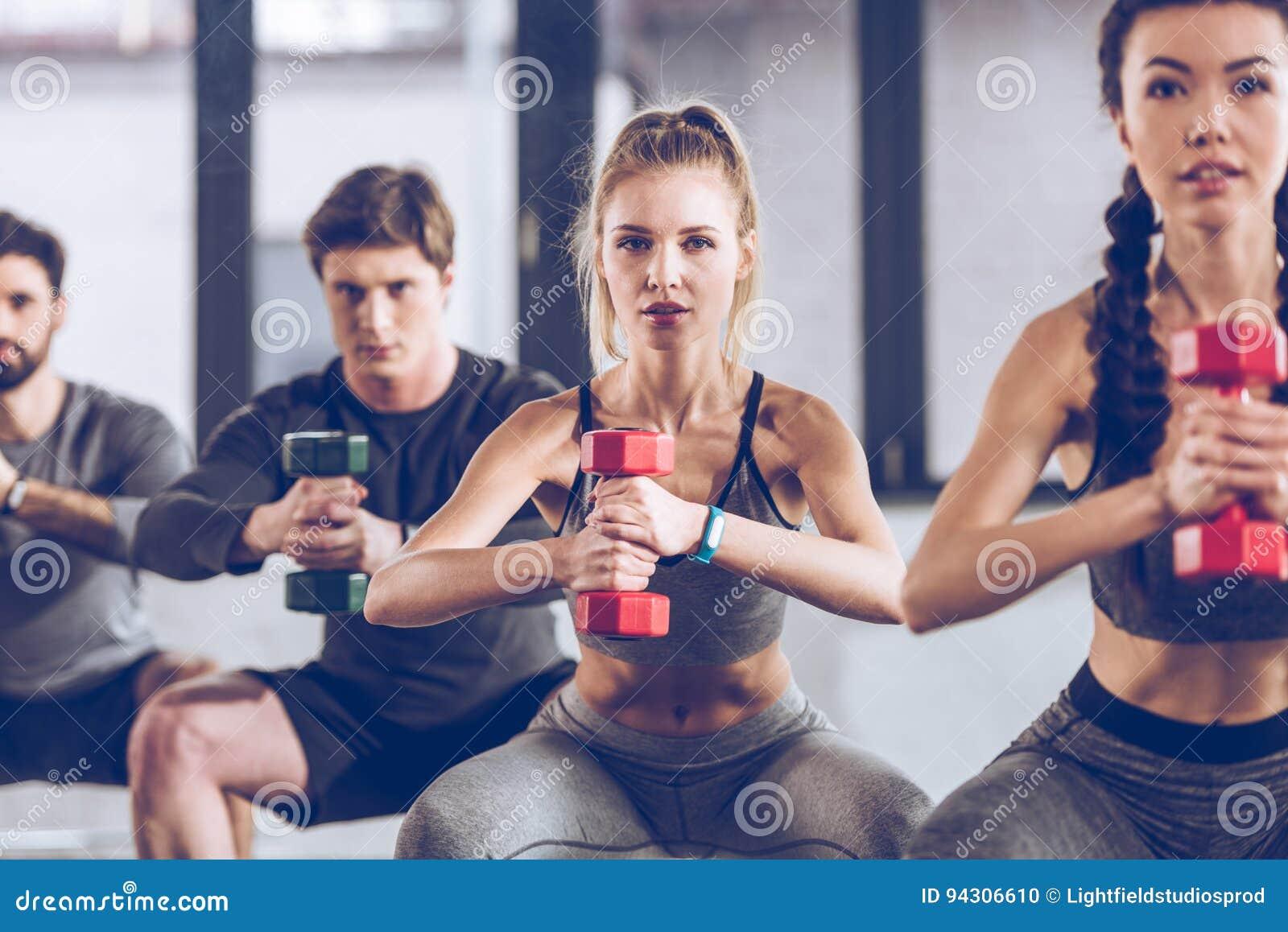 Jovens atléticos no sportswear com pesos que squatting e que exercitam no gym