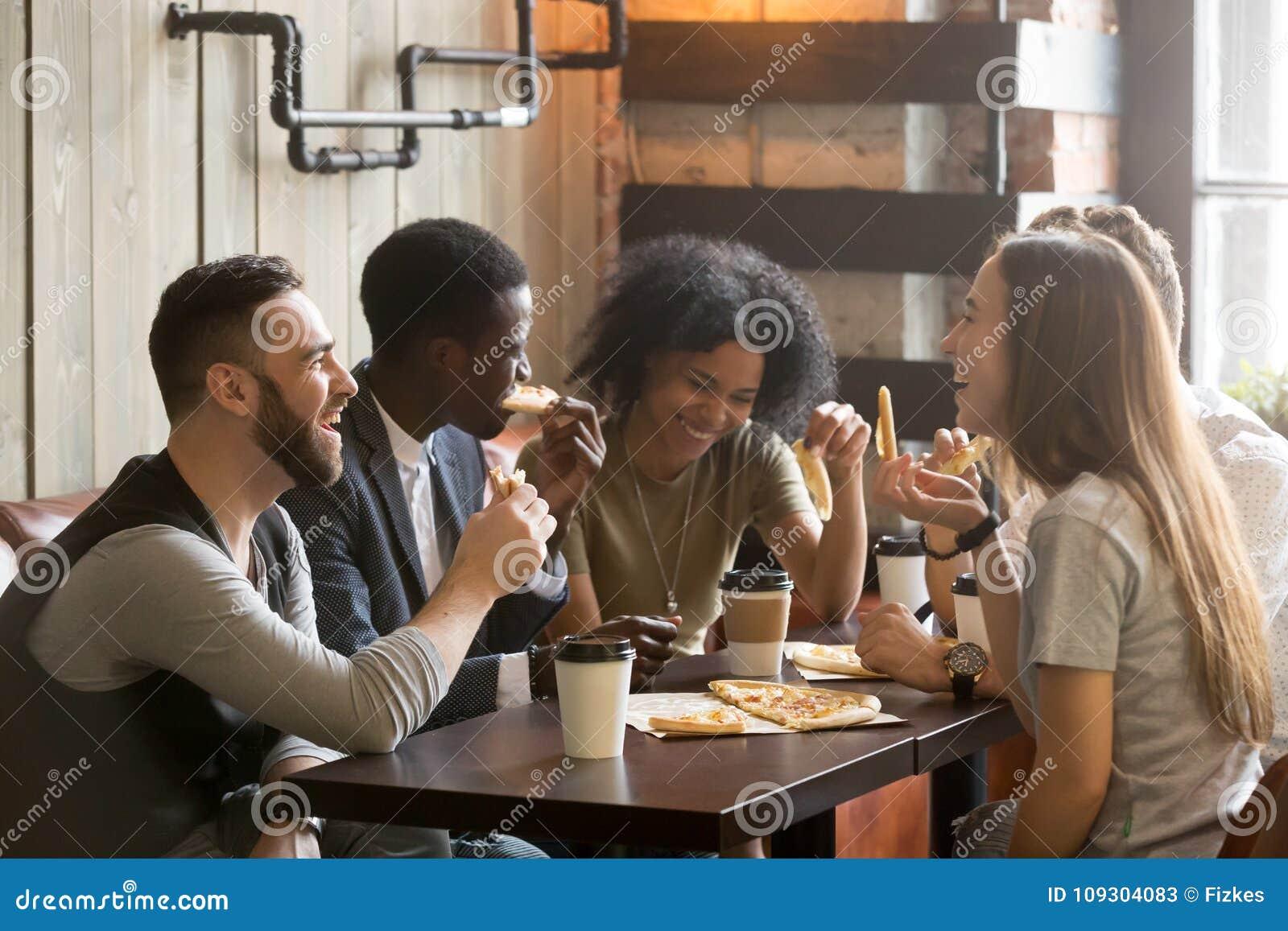 Jovens felizes multirraciais que riem comendo a pizza junto dentro