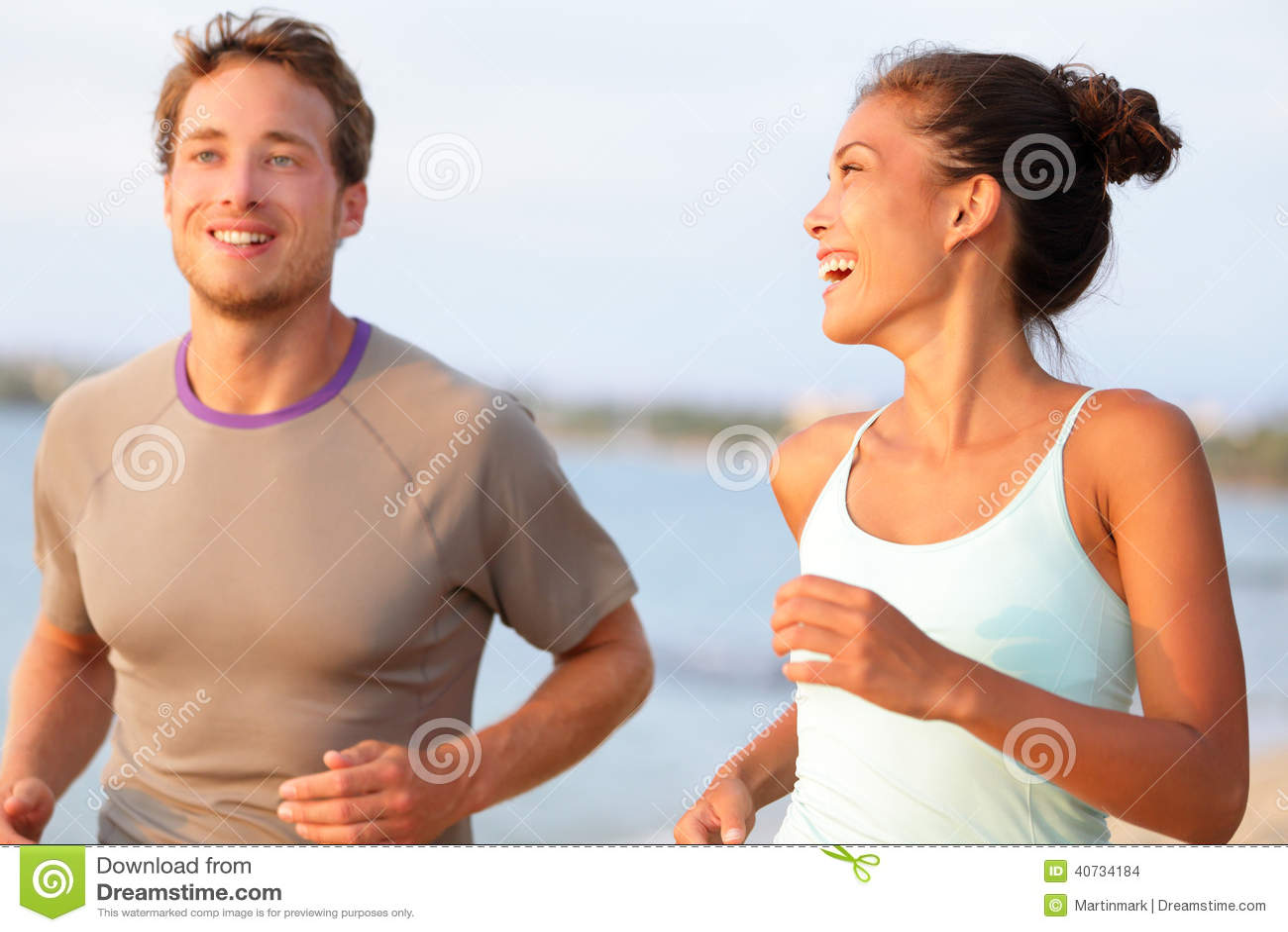 Jovens movimentando-se da aptidão que correm o sorriso feliz