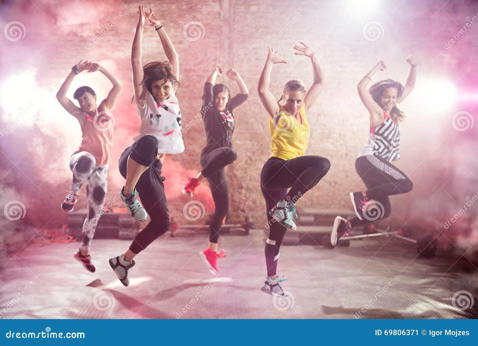 Jovens mulheres aptas que dançam e que exercitam