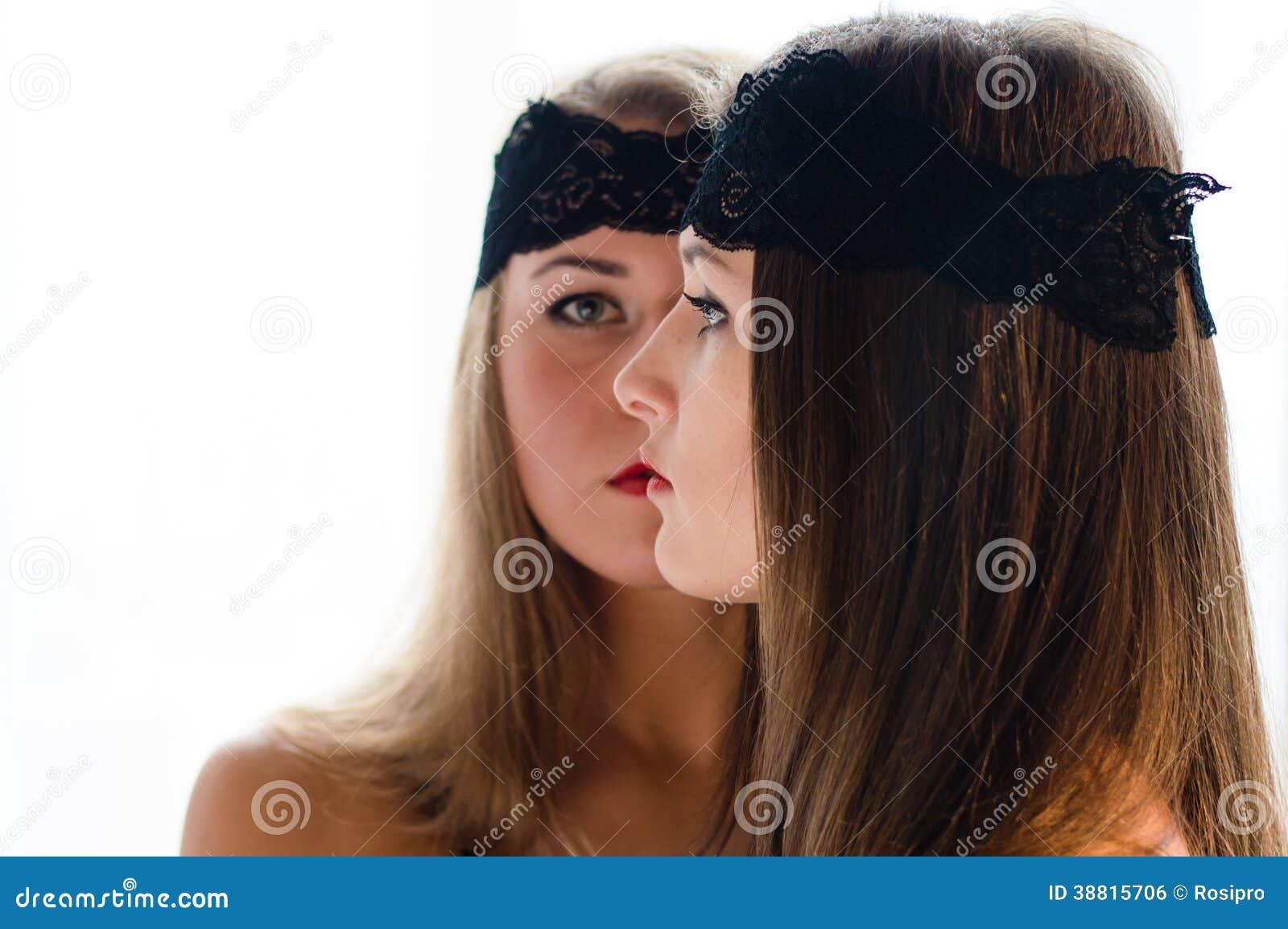 2 jovens mulheres bonitas do encanto com as faixas pretas no retrato do close up da cara