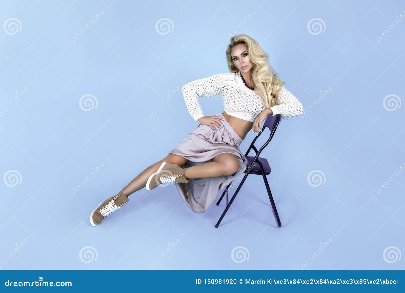 Jovens mulheres em sapatas à moda e no equipamento elegante no fundo da cor Modelo bonito no fundo azul