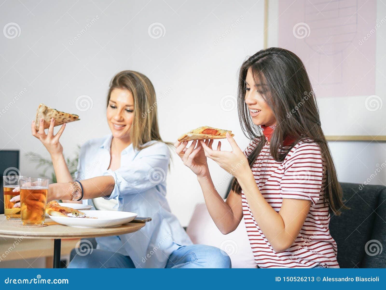 Jovens mulheres que comem a pizza do fast food e que bebem os amigos felizes da cerveja em casa - que apreciam um jantar que sent